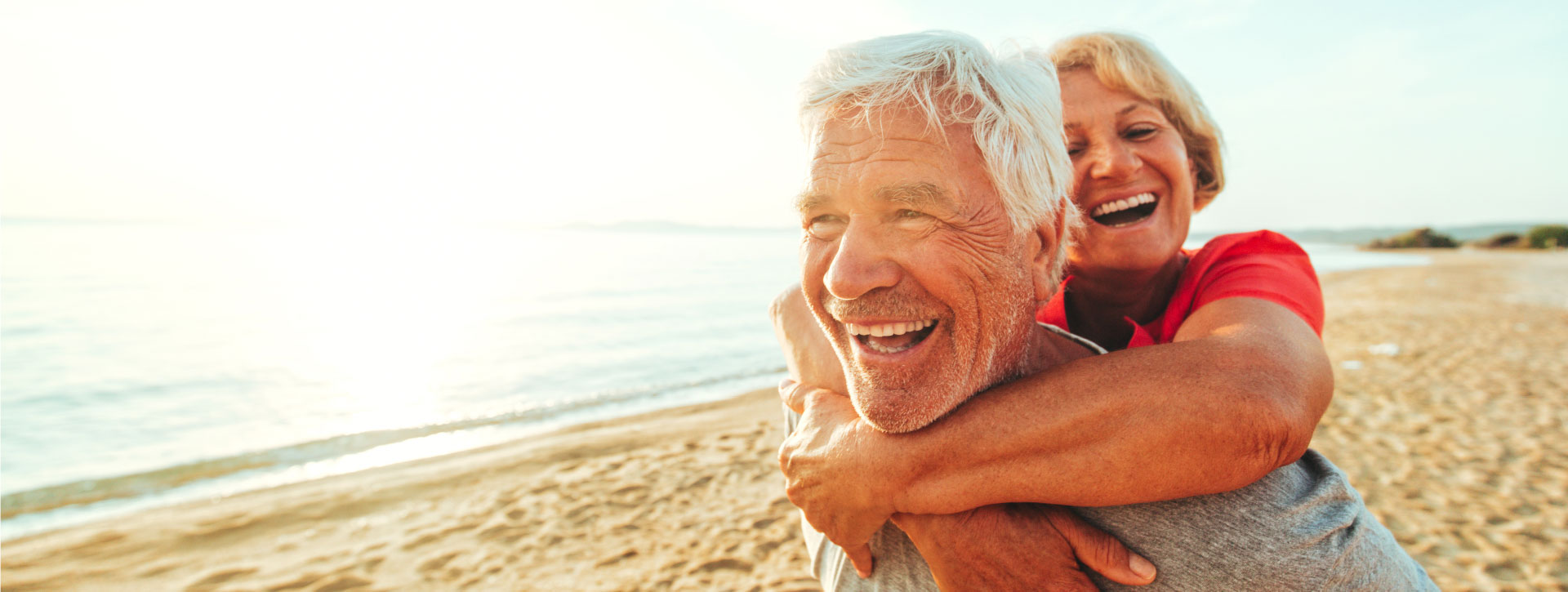 Man and woman embracing and smiling at beach